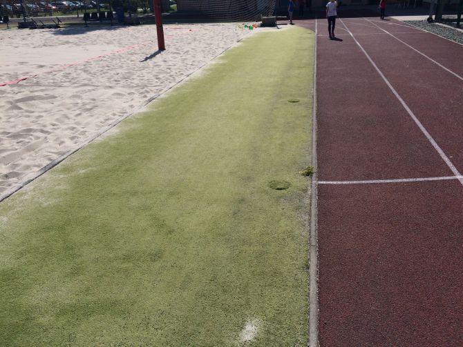 Čistenie umelej trávy a tartanovej dráhy v Karvinej v športovom areáli školy
